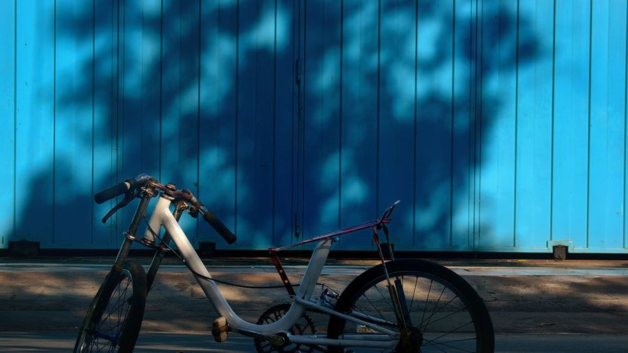 Bicycle parked on street against blue fence