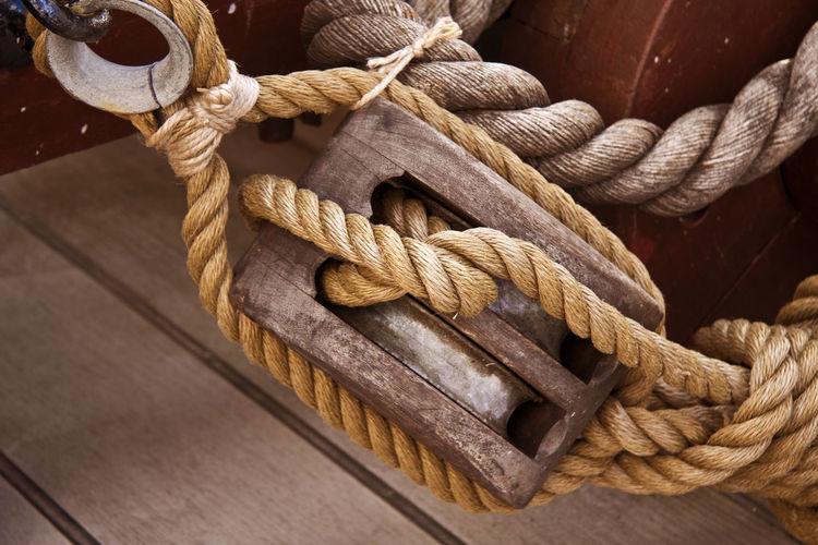 Close-up of ropes in wooden pulley