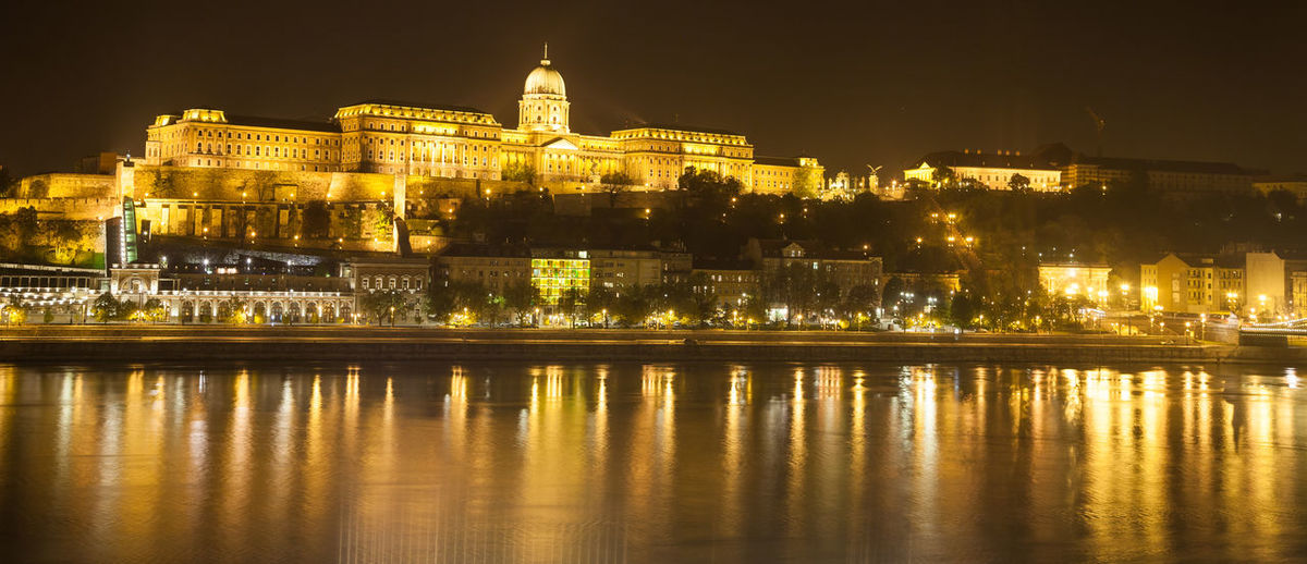 Illuminated buda castle by danube river against sky at night