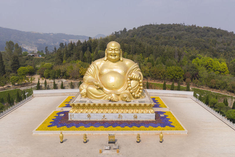Buddha statue against trees and mountains against sky