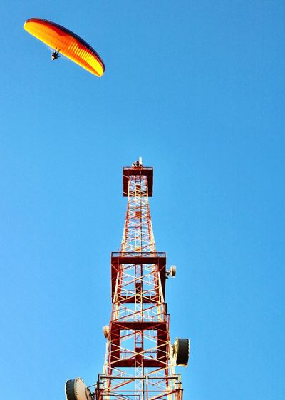 Low angle view of parachute over repeater tower against clear blue sky