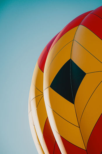 Low angle view of multi colored umbrella against clear blue sky
