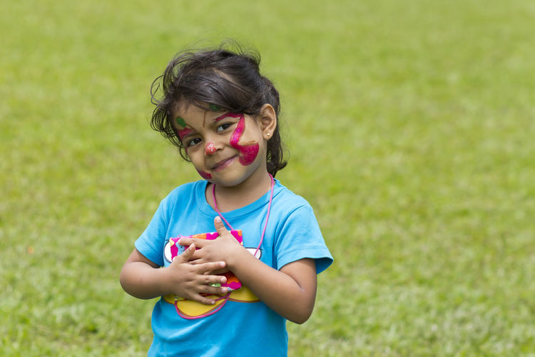 Portrait of girl with face paint standing on field