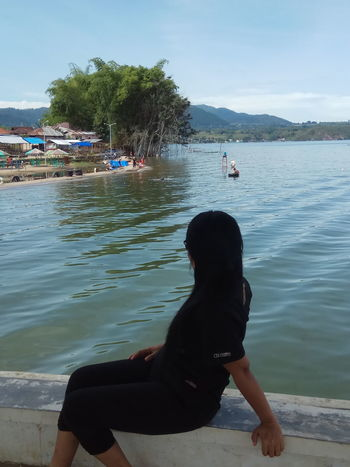 Holidays in Samosir Beauty In Nature Day Lake Nature One Person Outdoors Plant Real People Sitting Sky Tree Water