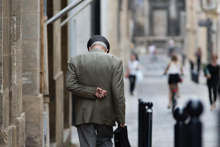 Rear view of old man walking on street