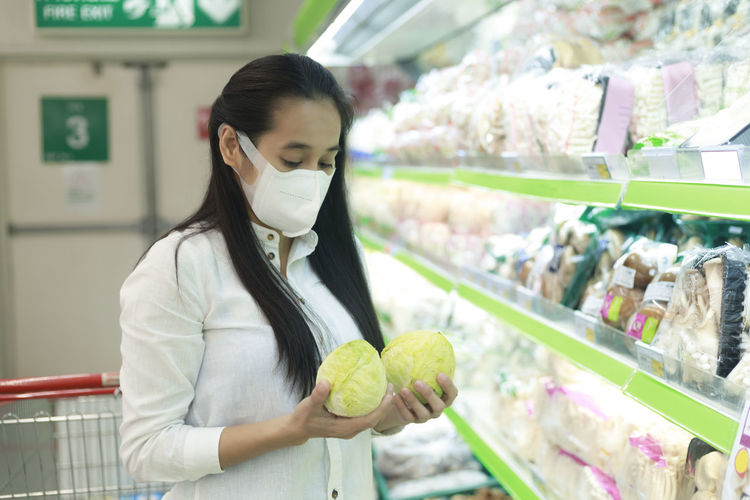 Close-up of woman wearing mask buying cabbages