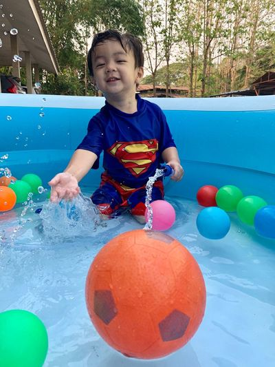 Childhood Child One Person Real People Males  Boys Happiness Men Smiling Enjoyment Front View Innocence Playing Emotion Ball Leisure Activity Lifestyles Day Fun Outdoors Swimming Pool