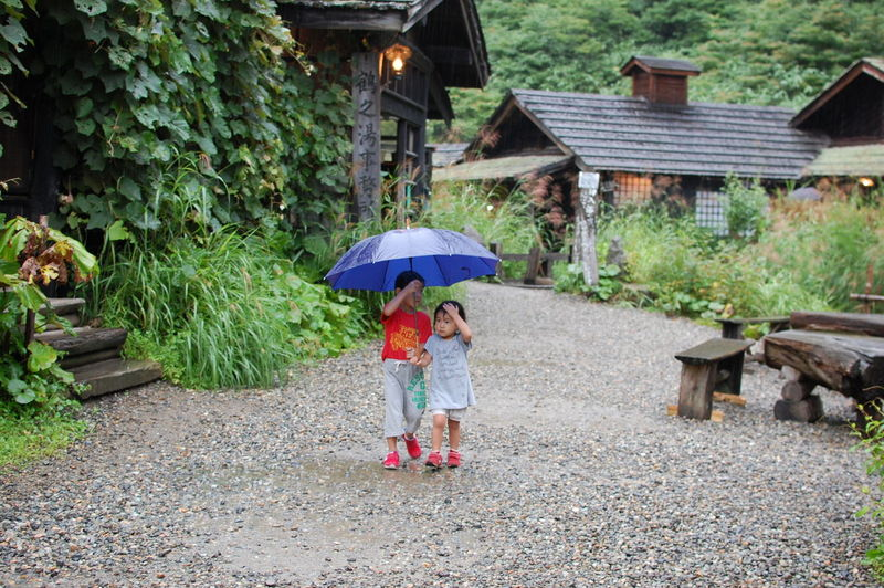 Siblings With Umbrella Walking On Dirt Road Amidst Houses