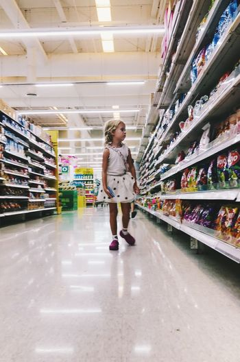 Full Length One Person Childhood Indoors  Store Shelf Women Casual Clothing Retail  Standing Lifestyles Supermarket Choice Real People Child Shopping Innocence Girls Consumerism Hairstyle