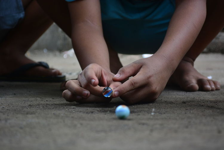 Low section of boy playing with marbles