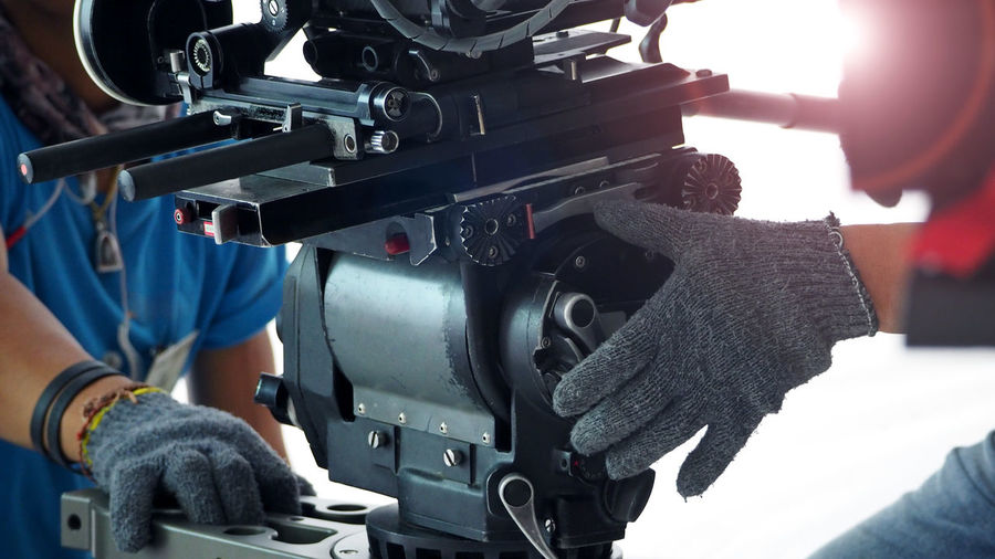 Cropped Hands Of Photographers Wearing Gloves While Operating Movie Camera