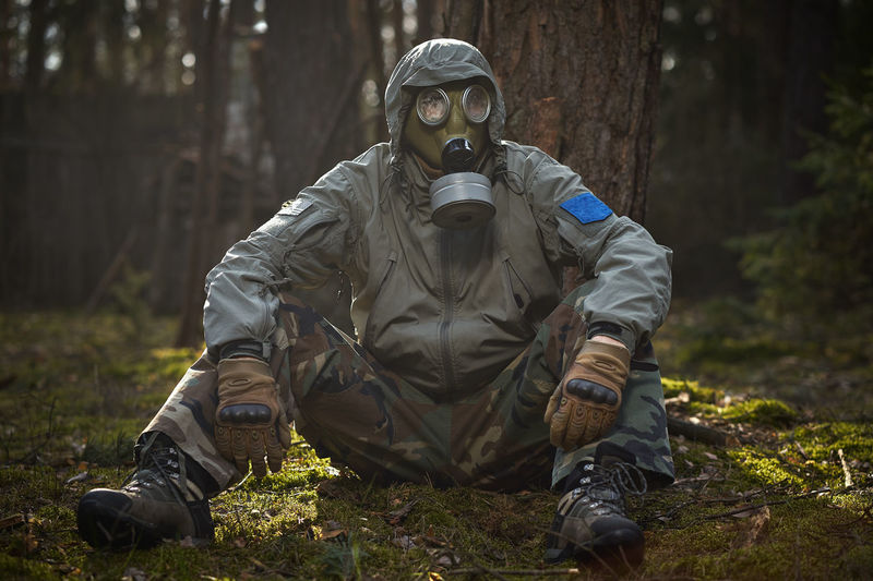 Midsection of person wearing mask against trees in forest