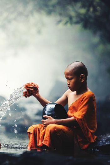 Monk splashing water in stream