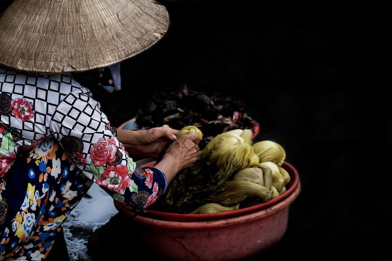 Woman with vegetables against black background