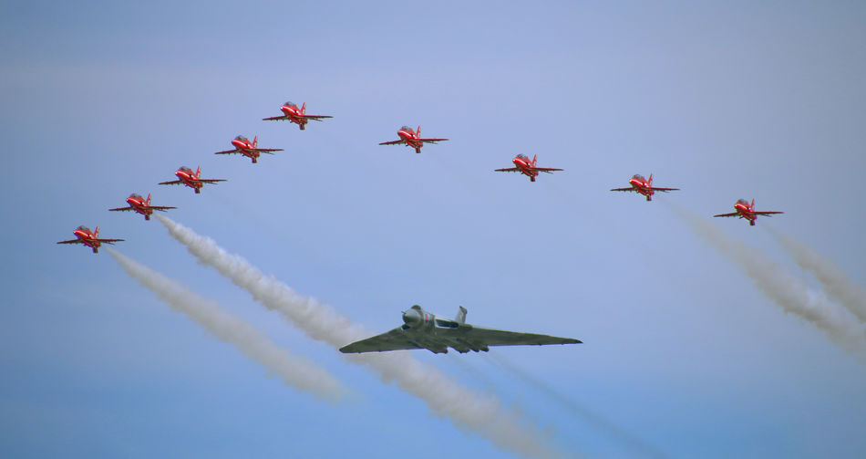 Low Angle View Of Red Arrows With Avro Vulcan Performing At Airshow