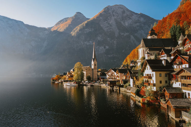 Panoramic View Of Lake By Buildings Against Mountains