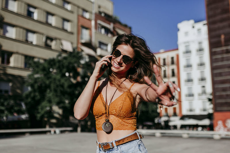 Portrait of young woman using phone while standing in city