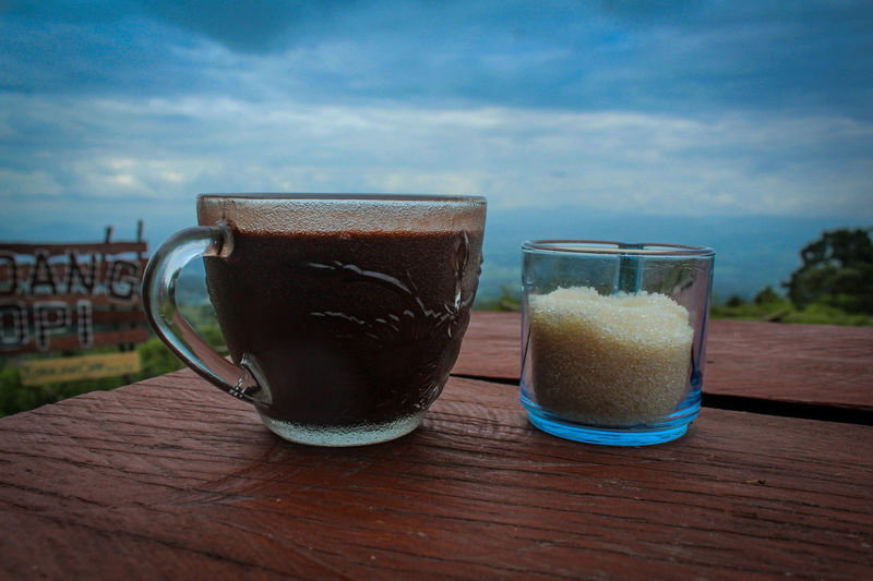 Close-up of coffee served on table against sky