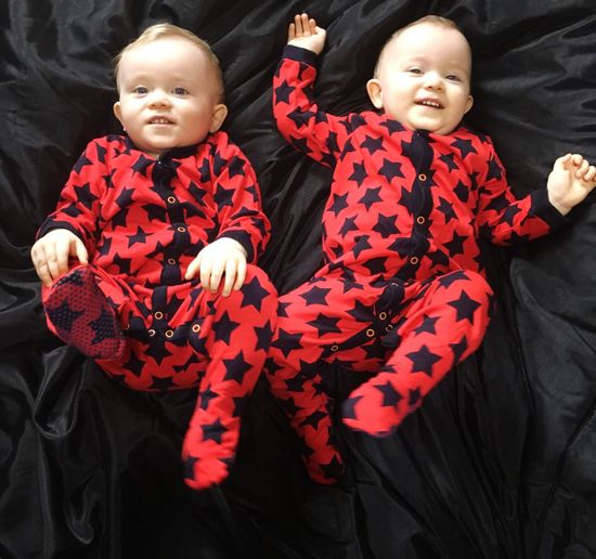 High angle view of twin toddlers lying on bed at home