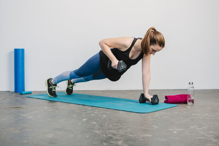 Young woman practicing plank pose with Weights Full Length One Person Lifestyles Sport Sports Clothing Young Women Indoors  Real People Young Adult Exercising Leisure Activity Healthy Lifestyle Balance Strength Concentration Women Adult Casual Clothing Hairstyle Effort Fitness Workout Working Working Out Inside Photography Horizontal Sport Clothes Sport Clothing Athlete