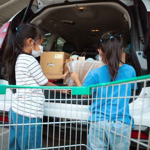 Sisters loading shopping bags in car trunk
