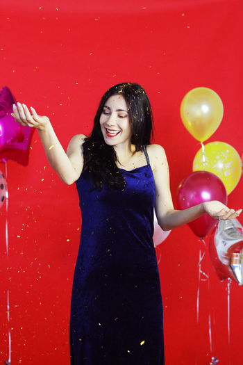 Smiling young woman standing with red balloon