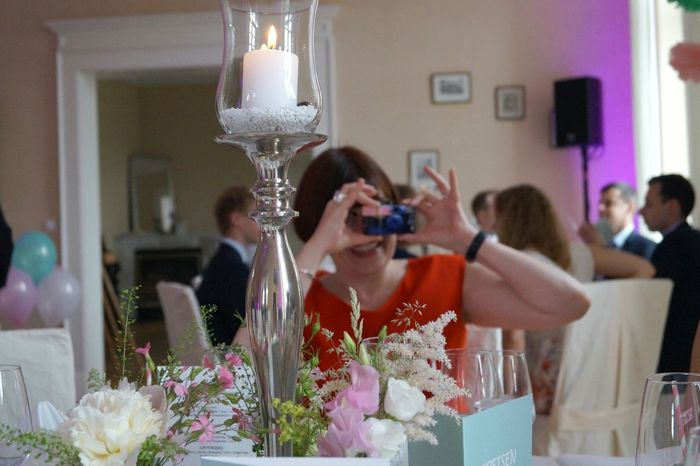 Guests taking photos Woman Taking Photos Of People Taking Photos Red Dress Sitting At The Table Vine Glasses Plates Champagne White Ribbons Drinking Straw Pink And White Stripes Pattern Napkin White Tablecloth Table Setting Wedding Decoration White Porcelain Pastel Colors Cutlery Candle Glasses Glass Of Water Summer Wedding  Flowers On Table Little Flags