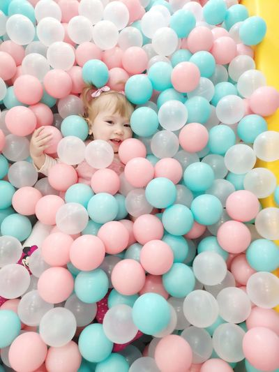 High angle view portrait of cute girl lying in ball of pool