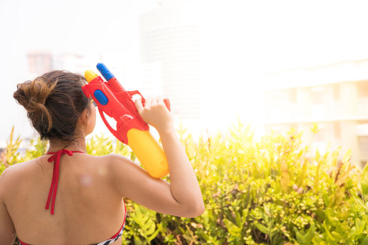 Rear View Of Woman Holding Squirt Gun Standing Outdoors