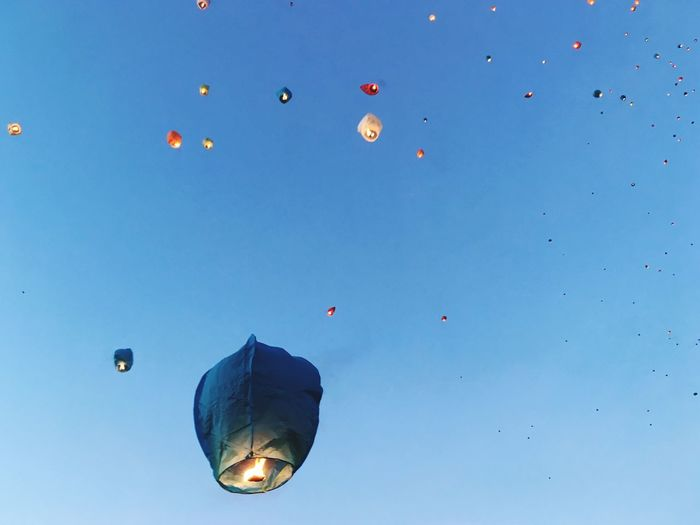 Low angle view of paper lanterns against clear blue sky