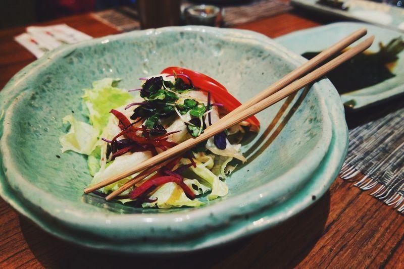 Vegetable salad and chopsticks on porcelain plate