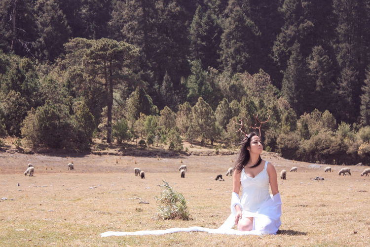 Woman with antler on hair in white dress sitting on field