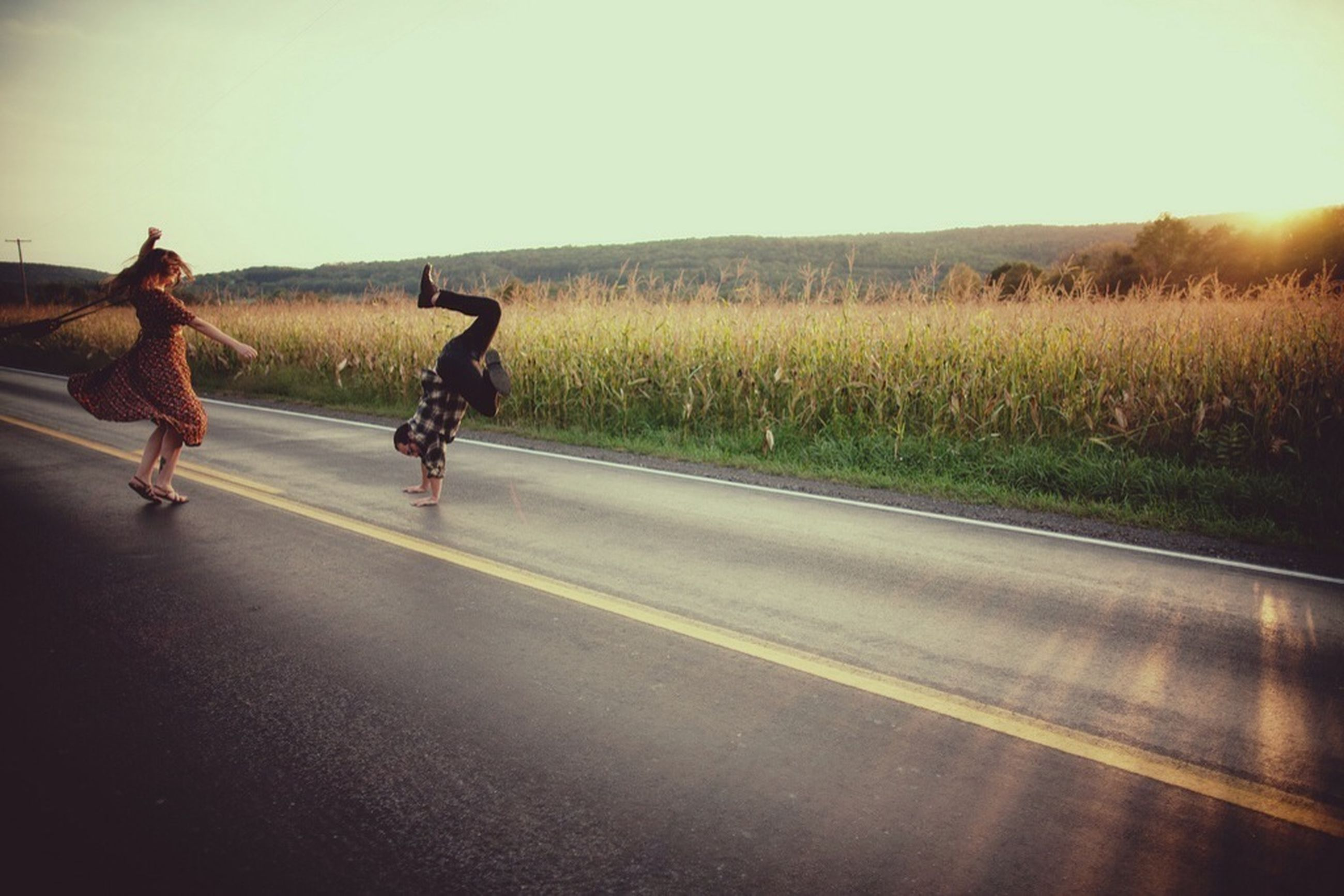 lifestyles, transportation, bicycle, full length, road, leisure activity, men, riding, clear sky, field, grass, land vehicle, landscape, walking, street, rear view, cycling, sunlight