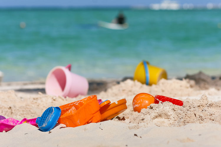 Close-up of multi colored toys on beach