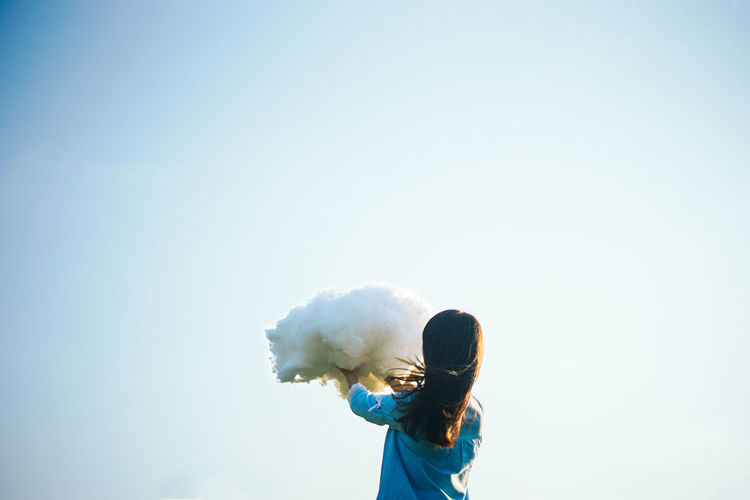 Girl holding up cloud against clear sky