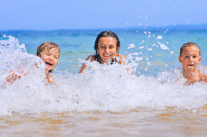 Portrait of happy woman and boys in sea