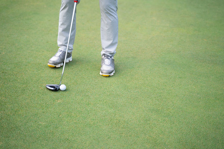 Low section of person standing on golf course