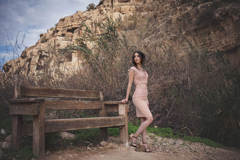 Side view of young woman posing while standing by bench against mountain