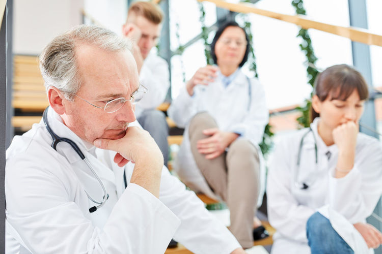 Worried doctors sitting on staircase at hospital