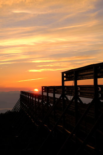 Silhouette railing by sea against orange sky
