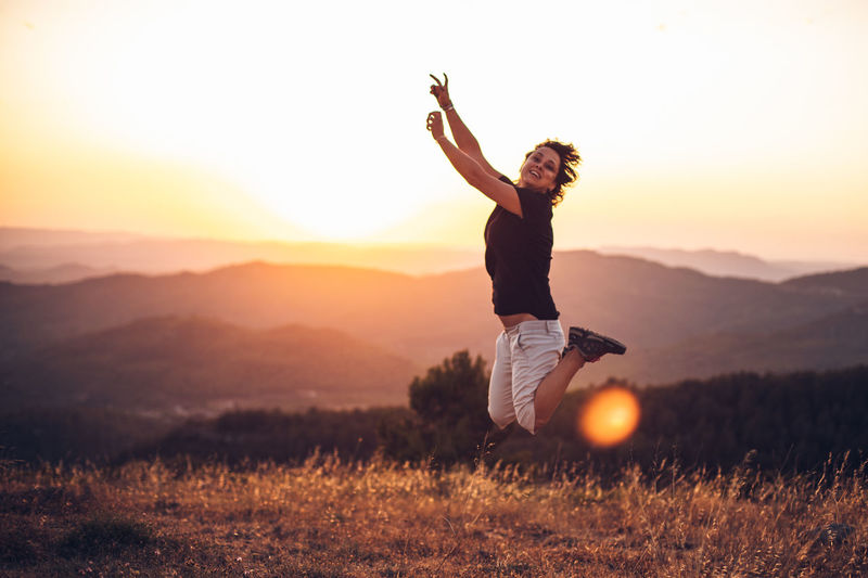 Man with arms raised on field against sky during sunset