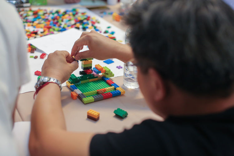 Rear view of man playing with blocks on table