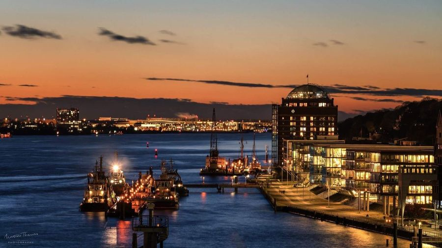 View of illuminated city at waterfront during sunset