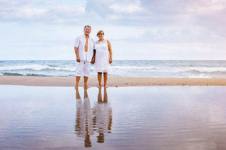Portrait Of Romantic Senior Couple Standing At Beach Against Sky
