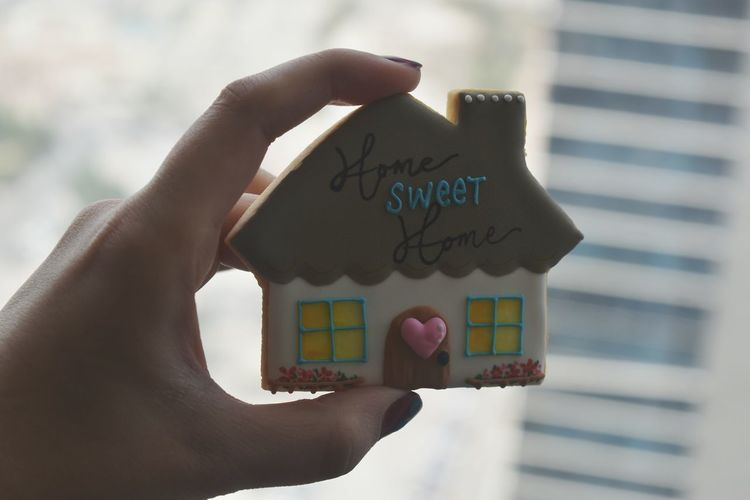Close-Up Of Person Holding Figurine House