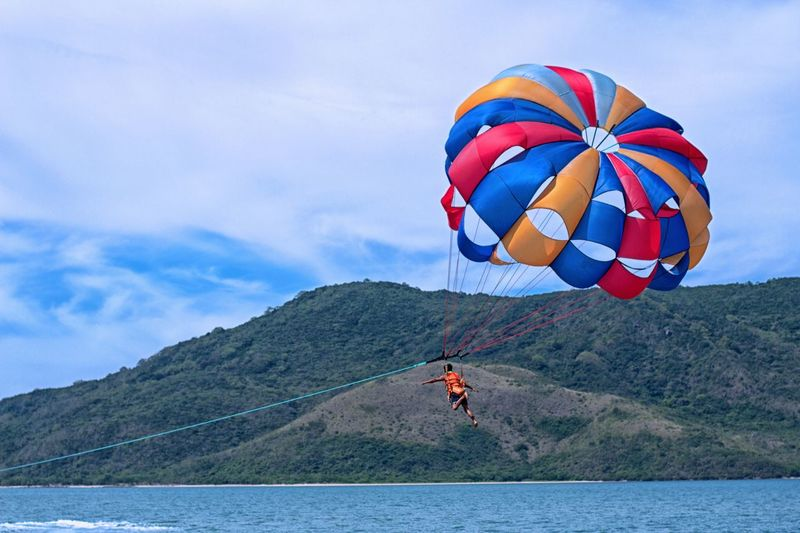 Rear View Of Man Paragliding Over Sea Against Sky