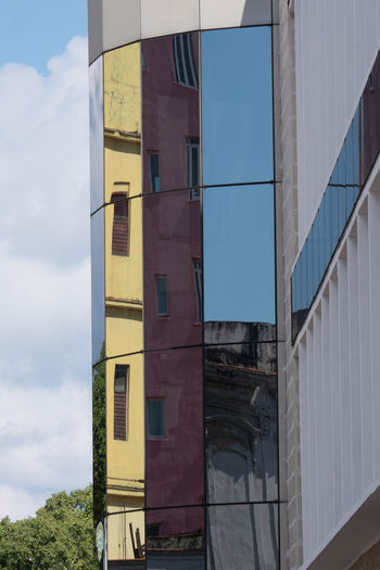 Clouds And Sky Cuba Cuba Collection Low Angle View Modern Architecture Reflections In The Glass Windows Travelling Photography Treetops Windows Yellow Color
