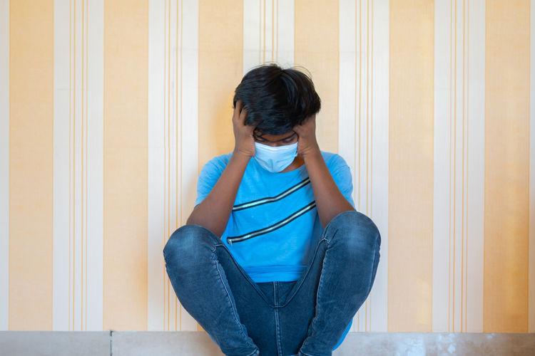 Full length of teenage girl sitting against wall