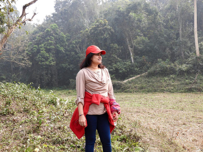 Full length of young woman standing against trees