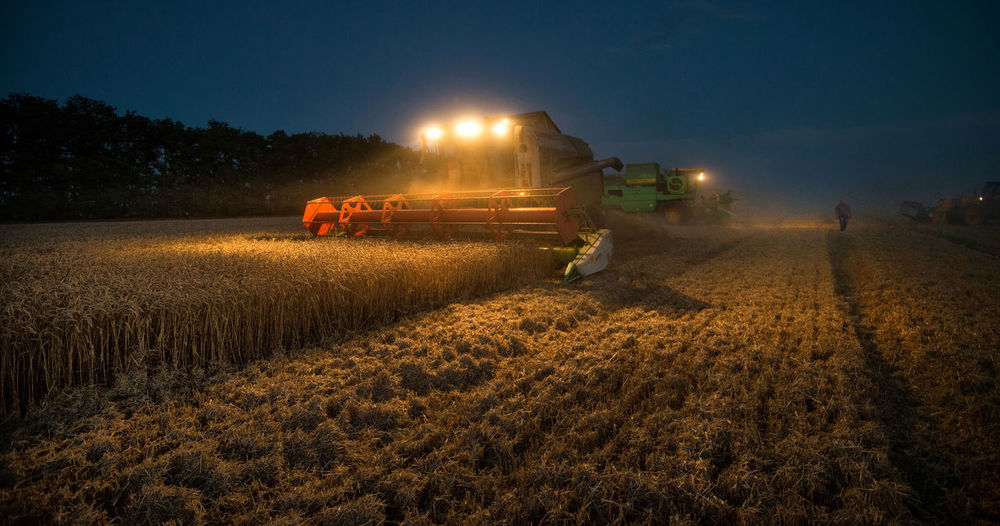 Machine harvesting crops on field at dusk